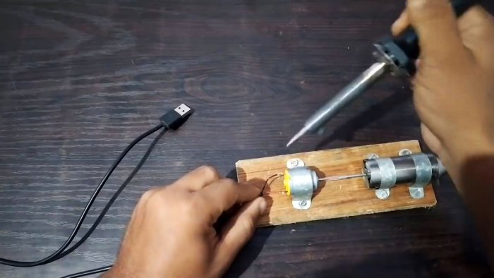 Wires are soldered to the contacts of the electric motor